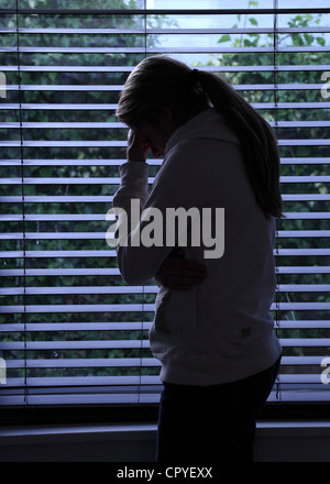 Profile of a girl with a ponytail, standing hands covering her face. Silhouette. - Stock Photo