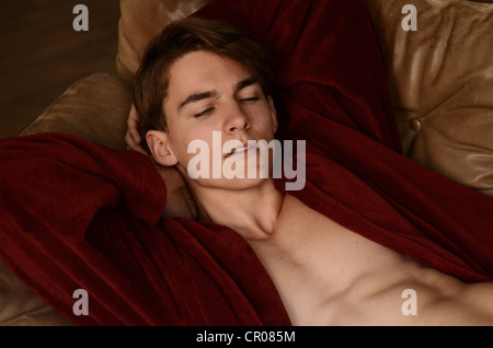 Young man wearing a red bath robe lying on a sofa - Stock Photo