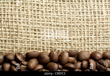 heap of coffee beans on burlap - Stock Photo