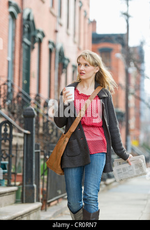 USA, New Jersey, Jersey City, Woman walking on street - Stock Photo