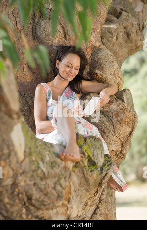 Smiling woman reading in tree - Stock Photo