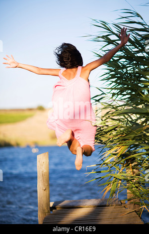 Woman jumping off dock into lake - Stockfoto