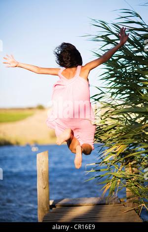 Woman jumping off dock into lake - Stockfoto