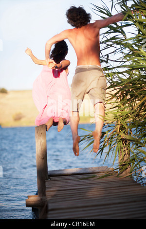 Couple jumping off dock into lake - Stockfoto