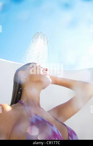 Woman in bikini showering outdoors - Stock Photo