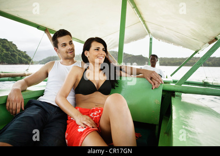 Couple relaxing on boat in river - Stock Photo