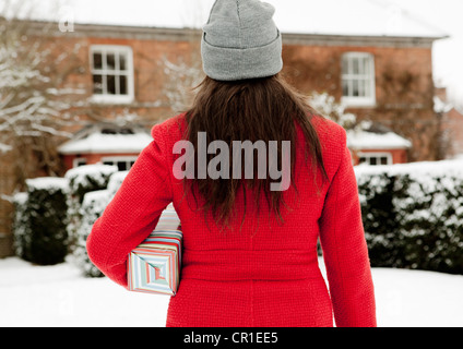 Woman carrying wrapped gift in snow - Stock Photo