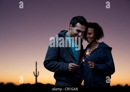 Couple playing with sparklers in desert - Stock Photo