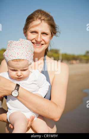 Smiling mother holding baby on beach - Stockfoto