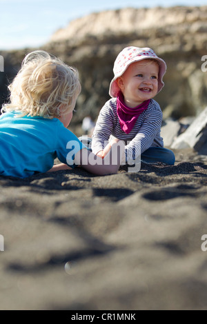 Boy playing with sibling on beach - Stock Photo