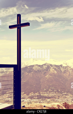 Cross on a hill, the Alps in the background - Stock Photo