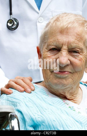 Senior Woman in Wheelchair with Doctor behind her - Stock Photo