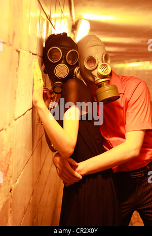 Married couple in gas masks in a tunnel - Stock Photo
