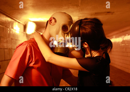 couple in the gas masks, kissing in the tunnel - Stock Photo