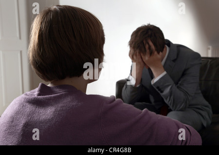 Back view of female looking at a man with his head in his hands. Both unrecognisable. - Stock Photo