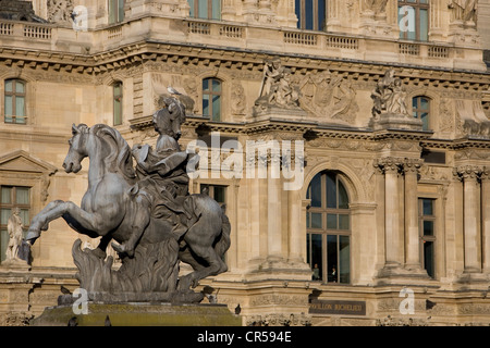 France, Paris, the Equestrian statue of Louis XIV in the Cour Napoleon of the Louvre Museum and the facade of the - Stock Photo