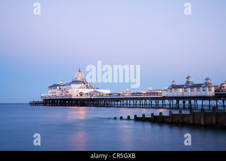 The pier at Eastbourne, Sussex, illuminated at twilight on a perfectly clear summer evening. - Stock Photo