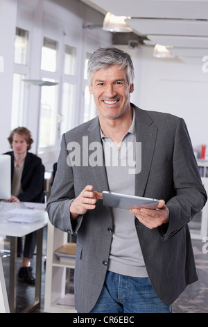Germany, Bavaria, Munich, Mature man using digital tablet, colleague working in background - Stock Photo
