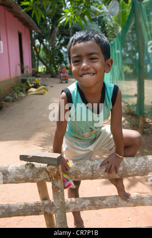 Smiling boy climbing on a fence with their mother sitting behind, Kanjippadom, near Alappuzha (Alleppey), Kerala, - Stock Photo