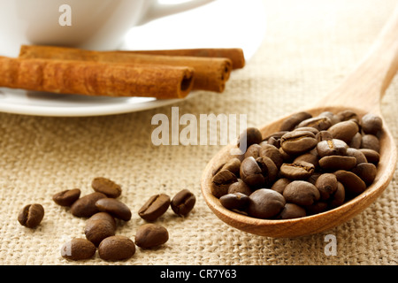 Coffee Beans in a Wooden Spoon with Cinnamon Sticks and Coffee Mug - Stockfoto