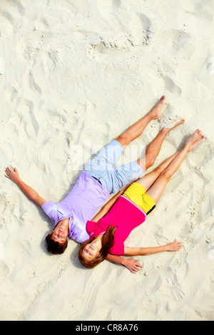 Above angle of two teenage friends lying on sandy beach with closed eyes - Stock Photo