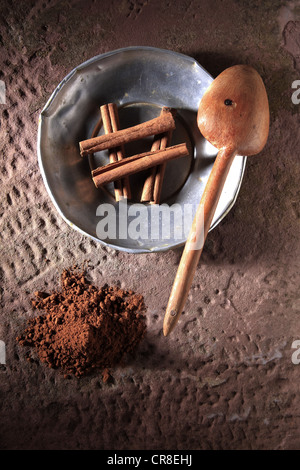 Cinnamon sticks (Cinnamomum) on a metal plate with a wooden spoon and cinnamon powder on a rustic stone base - Stock Photo