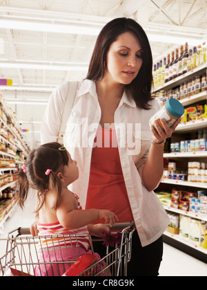 Mother reading label on baby food jar in supermarket - Stock Photo