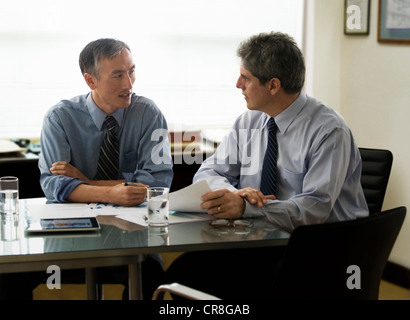 Businessmen discussing report in office - Stock Photo