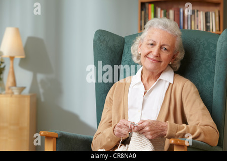 Senior woman knitting, portrait - Stock Photo