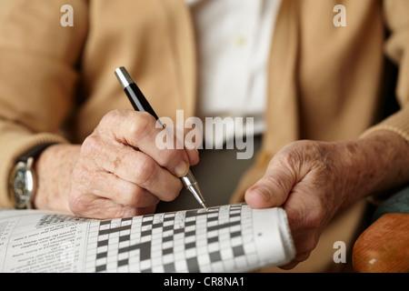 Senior woman doing crossword - Stockfoto