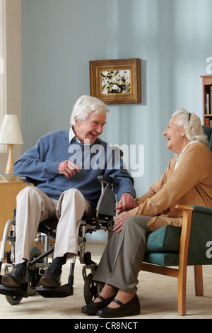 Senior couple in care home, man in wheelchair - Stock Photo