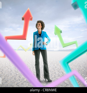 Businesswoman looking at holographic arrows in desert - Stock Photo
