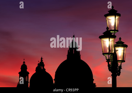 Lamp post in front of Santa Maria della Salute at sunset, Venice, Italy, Europe - Stock Photo