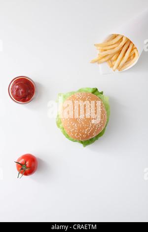 Fast food, burger, fries, ketchup, tomato - Stock Photo