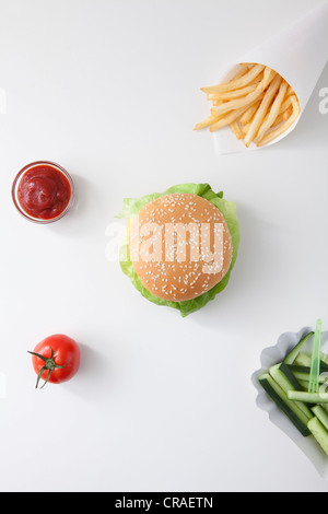 Fast food, burger, fries, ketchup, tomato, cucumbers - Stock Photo