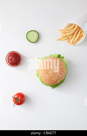 Fast food, burger, fries, ketchup, tomato, slice of cucumber - Stock Photo