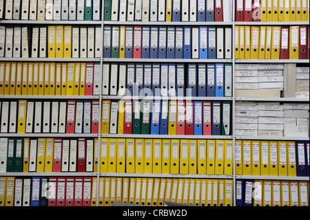 Coloured file folders on a shelf - Stock Photo