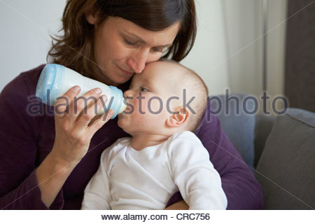 Mother bottle feeding baby on sofa - Stock Photo