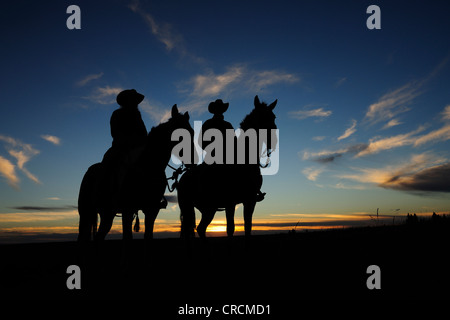 A cowgirl and a cowboy sitting on their horses in the sunset, Saskatchewan, Canada - Stock Photo