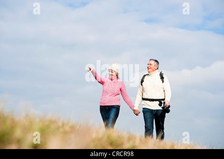 Couple walking hand in hand in meadow - Stock Photo