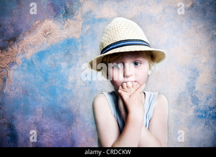 Five-year-old boy wearing a hat, sad face, portrait - Stock Photo