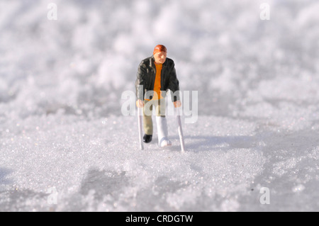 Figure with leg in plaster in snow - Stock Photo