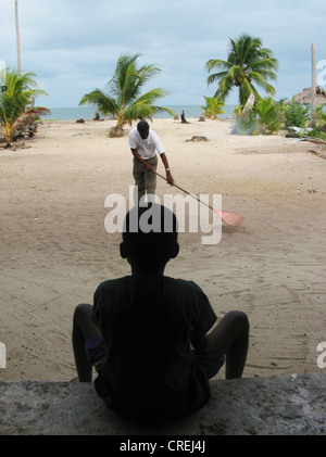 Young Garifuna, a descendant of black slaves, sitting in the shade, Belize, Stann Creek District, Hopkins - Stock Photo