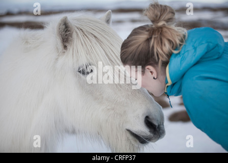 Woman kissing white horse in snow - Stock Photo