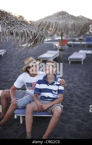 Brothers laughing together on beach - Stock Photo