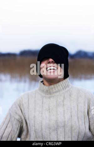 Mann mit Hut über Augen im Schnee - Stockfoto