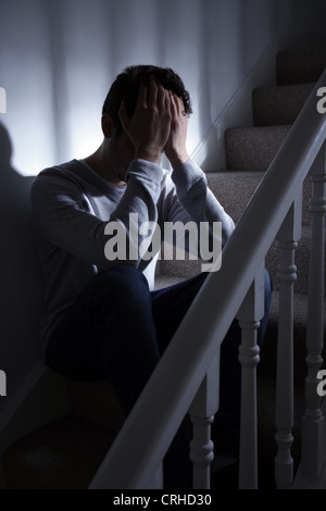 Young man sitting on the stairs with his hands covering his face. - Stock Photo