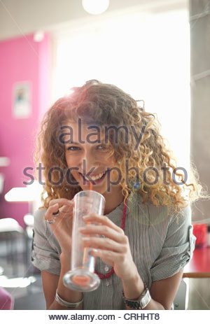 Smiling woman drinking in cafe - Stock Photo