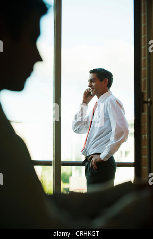 Silhouette of businessman using cell phone by window - Stock Photo