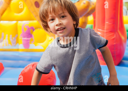 Boy playing in bouncy castle, portrait - Stock Photo